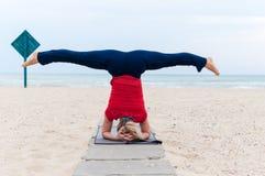 Woman doing yoga asana upavishtha konasana shirshasana, Bound Angle Pose in Head Stand on sea background Stock Image