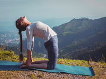 Woman doing yoga asana Ustrasana camel pose outdoors Royalty Free Stock Image