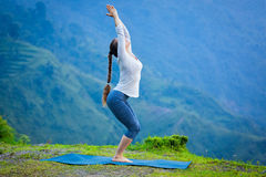 Woman doing yoga asana Utkatasana outdoors Royalty Free Stock Images