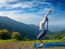 Woman doing yoga asana Utkatasana outdoors. Young sporty fit woman doing yoga asana Utkatasana (chair pose) outdoors in mountains Himalayas in the morning Stock Image