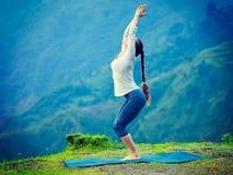 Woman doing yoga asana Utkatasana outdoors. Young sporty fit woman doing yoga asana Utkatasana chair pose outdoors in mountains Himalayas in India. Vintage retro Stock Photo