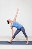 Woman doing yoga asana utthita trikonasana Royalty Free Stock Photography