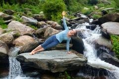 Woman doing yoga asana Vasisthasana - side plank pose outdoors Royalty Free Stock Photos