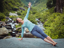 Woman doing yoga asana Vasisthasana - side plank pose outdoors Royalty Free Stock Photo