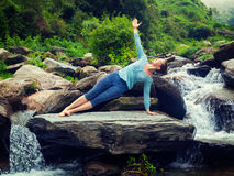 Woman doing yoga asana Vasisthasana - side plank pose outdoors Royalty Free Stock Images