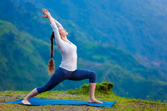 Woman doing yoga asana Virabhadrasana 1 - Warrior pose outdoors Stock Images