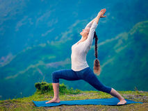 Woman doing yoga asana Virabhadrasana 1 - Warrior pose outdoors Royalty Free Stock Photo