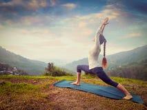 Woman doing yoga asana Virabhadrasana 1 - Warrior pose outdoors Stock Photo