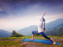 Woman doing yoga asana Virabhadrasana 1 - Warrior pose outdoors Royalty Free Stock Photography