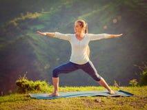 Woman doing yoga asana Virabhadrasana 2 - Warrior pose outdoors Royalty Free Stock Photo