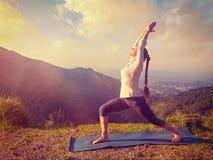 Woman doing yoga asana Virabhadrasana 1 - Warrior pose outdoors Royalty Free Stock Photo