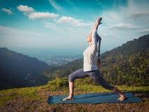 Woman doing yoga asana Virabhadrasana 1 - Warrior pose outdoors Royalty Free Stock Photography