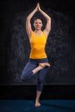 Woman doing yoga asana Vrikshasana tree po Stock Photography