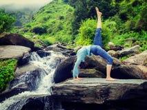 Woman doing yoga asana at waterfall Royalty Free Stock Photo
