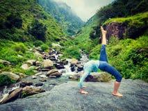 Woman doing yoga asana at waterfall Royalty Free Stock Photos