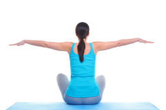 Woman doing yoga balance. Rear view of a brunette woman sat on a yoga mat with her arms out in a balance position. Isolated on a white background Stock Images