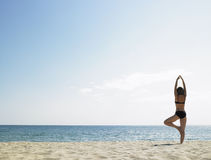 Woman Doing Yoga at the Beach Royalty Free Stock Photography