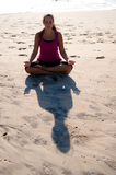 Woman doing yoga on beach. Royalty Free Stock Image