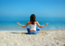 Woman doing yoga on the beach. Young attractive female sits on a beach doing yoga with a view of the Adriatic Sea from Gargano National Park in Southern Italy Stock Photo