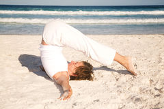 Woman doing yoga on the beach Stock Images