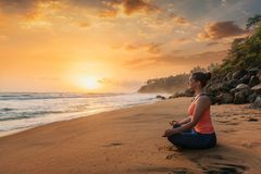 Woman doing yoga at beach - Padmasana lotus pose. Woman doing yoga - meditate and relax in Padmasana Lotus asana pose with chin mudra outdoors at tropical beach Stock Image