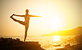 Woman doing yoga on the beach at sunset Stock Photos