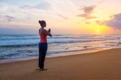 Woman doing yoga on beach stock photo