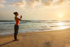 Woman doing yoga on beach stock photo