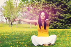 Woman doing yoga. Beautiful brunette doing yoga exercise and meditation, outdoors Royalty Free Stock Photography