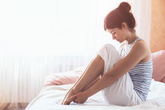 Woman doing yoga in the bed. Woman doing yoga exercise on bed at home. Morning workout in bedroom. Healthy and sport lifestyle Stock Images