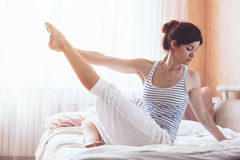 Woman doing yoga in the bed Royalty Free Stock Image