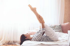 Woman doing yoga in the bed Royalty Free Stock Photo