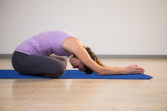 Woman doing yoga child pose on exercise mat Stock Photography