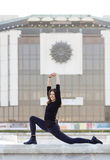 Woman doing yoga in city. Woman dressed in black performing yoga outdoors in modern urban setting Stock Image