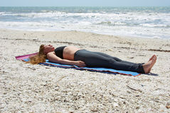 Woman doing yoga corpse pose on beach. An athletic brown haired woman is doing yoga exercise Savasana or corpse pose on an empty beach at the gulf of mexico in Stock Photography