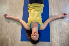 Woman doing yoga corpse pose on exercise mat. In fitness studio royalty free stock image
