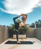 Woman doing yoga dancer pose on the rooftop royalty free stock images