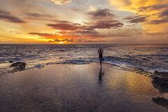 Free Woman Doing Yoga During The Sunset Falling Over The Sea Stock Photos - 182392733