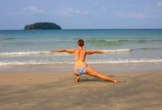 Woman doing yoga on empty beach. Tropical seaside vacation activity. Young girl in asana posture. Meditation on seashore. White sand beach view with woman in Stock Images