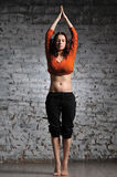 Woman doing yoga excercise. Full-length portrait of young beautiful woman doing yoga excercise against a brick wall Royalty Free Stock Images
