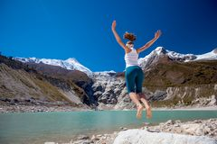 Woman is doing yoga excercises near big lake on the Manaslu circ Stock Images