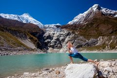 Woman is doing yoga excercises near big lake on the Manaslu circ Royalty Free Stock Image