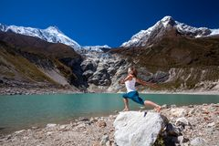 Woman is doing yoga excercises near big lake on the Manaslu circ Royalty Free Stock Photography