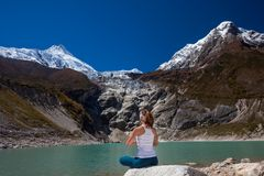 Woman is doing yoga excercises near big lake on the Manaslu. Circuit trak in Nepal Stock Photo