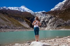 Woman is doing yoga excercises near big lake on the Manaslu circ. Uit trak in Nepala Royalty Free Stock Images