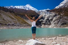 Woman is doing yoga excercises near big lake on the Manaslu circ Stock Image