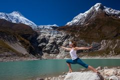 Woman is doing yoga excercises near big lake on the Manaslu. Circuit trak in Nepal Royalty Free Stock Photography
