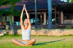 Woman doing yoga exercise. Beautiful young woman doing yoga exercise outdoors Royalty Free Stock Images