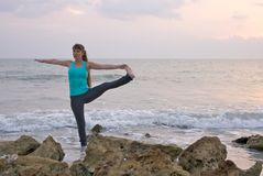 Woman doing yoga exercise at  beach Royalty Free Stock Photo