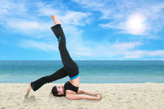 Woman doing yoga exercise on the beach Stock Images